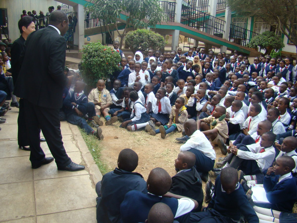James Mwangi talking to a large crowd of schoolchildren